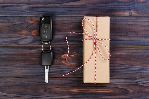 Chiave dell'automobile vicino alla scatola di carta con l'arco rosso del nastro sul fondo di legno della tavola