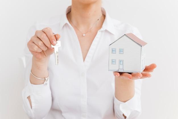 Chiave della tenuta e della donna e piccola casa di carta sopra fondo bianco