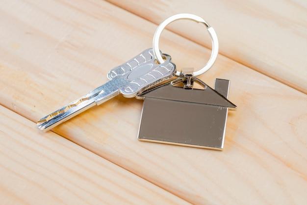 Chiave di casa con portachiavi casa sul tavolo di legno