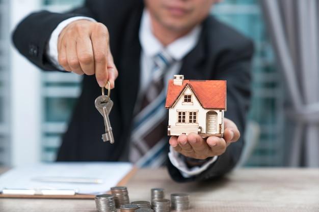 Chiave di casa nella protezione della mano dell'agente di brokeraggio assicurativo domestico o nella persona del venditore che consegna a