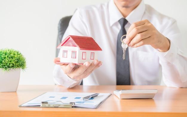 Chiave di casa nella protezione delle mani dell'agente broker di assicurazione casa