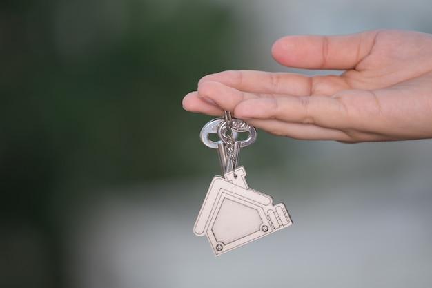 Chiave domestica della tenuta della mano della donna. concetto per il settore immobiliare.