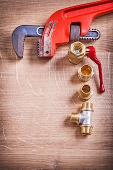 Chiave inglese di copysoace organizzata vista aerea e connettori di tubo d'ottone sul bordo di legno