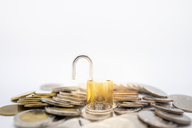 Chiave principale dorata sbloccata sulla pila e sul mucchio di monete su bianco