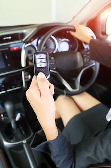 Chiave remota di manifestazione della donna di affari in automobile moderna del veicolo.