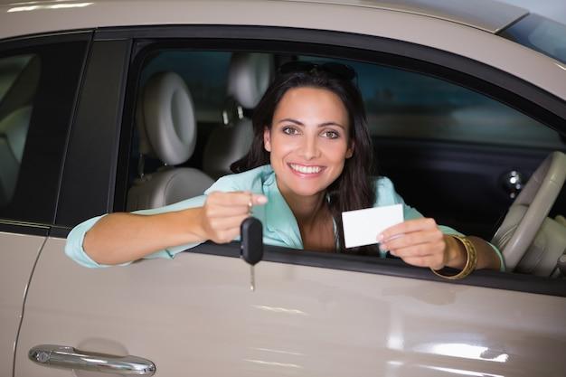 Chiave sorridente della donna della tenuta della tenuta e biglietto da visita
