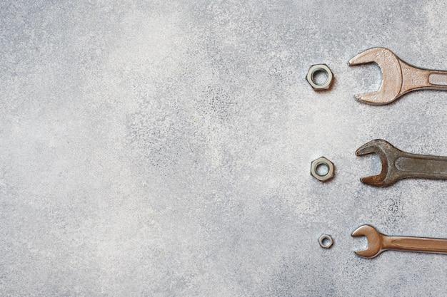 Chiavi, bulloni degli strumenti e dadi su fondo concreto grigio con lo spazio della copia.