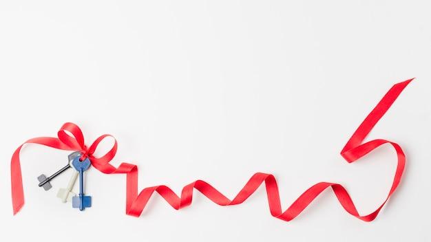 Chiavi con nastro rosso isolato su sfondo bianco