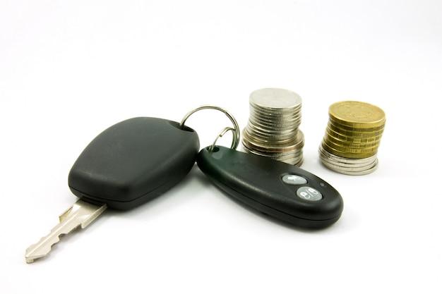 Chiavi dell'automobile con l'allarme e le monete telecomandati dell'automobile su una parete bianca