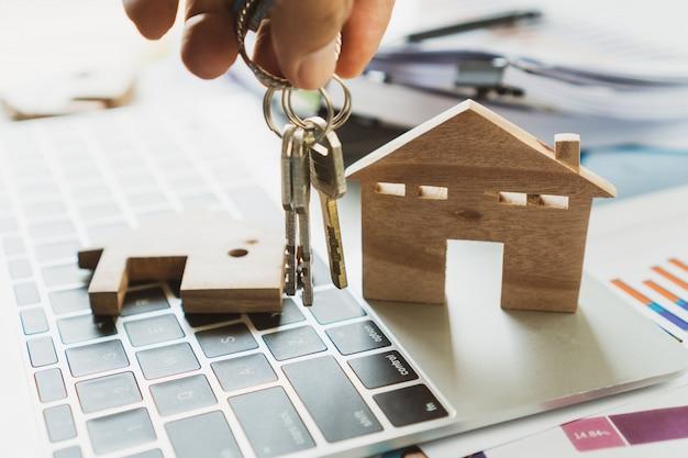 Chiavi della tenuta del proprietario-casa con il modello domestico di legno sul rapporto del grafico del computer