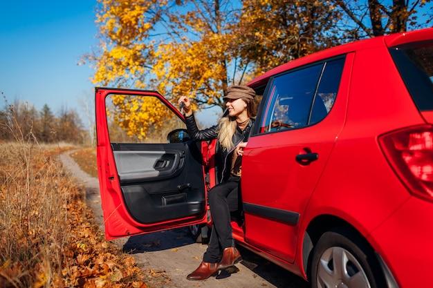 Chiavi della tenuta della donna di nuova automobile. l'acquirente felice ha acquistato l'autimobile rosso. autista seduto in auto