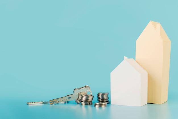 Chiavi di casa; pila di monete vicino alle case di carta contro il contesto blu