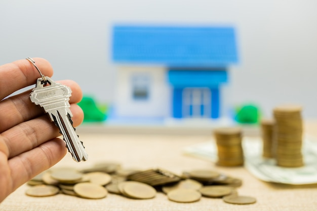Chiavi e pile di denaro e case