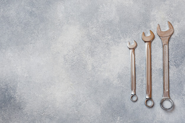 Chiavi, strumenti su sfondo grigio cemento con spazio di copia.