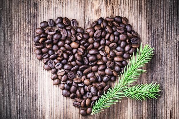Chicchi di caffè a forma di cuore con ramo di abete sulla superficie in legno