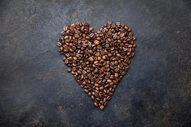 Chicchi di caffè a forma di cuore su rustico scuro