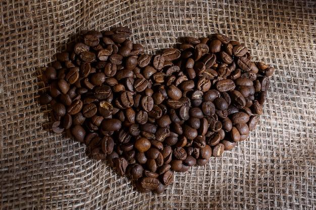 Chicchi di caffè a forma di cuore su una tela ruvida