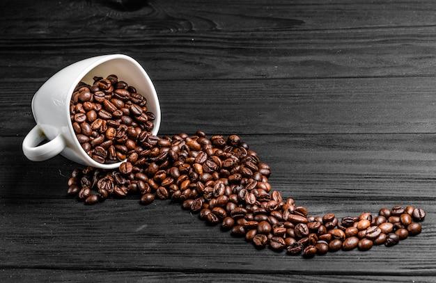 Chicchi di caffè arrostiti che si rovesciano da una tazza bianca sulla tavola di legno.