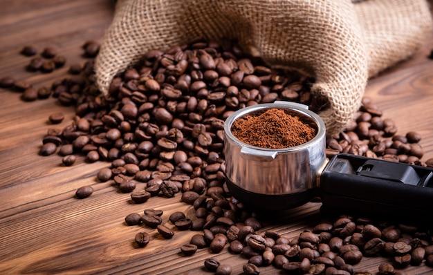 Chicchi di caffè arrostiti che si svegliano da una borsa di caffè della iuta. porta filtro con caffè macinato su uno sfondo di legno vintage marrone.