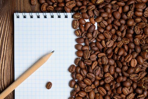 Chicchi di caffè arrostiti con il blocco note di carta e la priorità bassa della matita