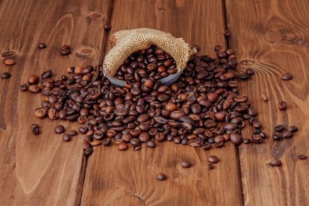 Chicchi di caffè arrostiti freschi che cadono dal sacco sulla superficie di legno. chicchi di caffè marrone sparsi dalla borsa sul tavolo
