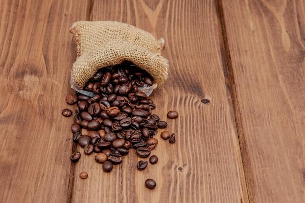 Chicchi di caffè arrostiti freschi che cadono dal sacco sulla superficie di legno.