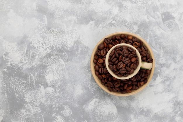Chicchi di caffè arrostiti freschi su calcestruzzo, vista superiore, disposizione piana