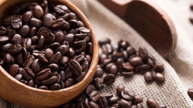 Chicchi di caffè arrostiti in ciotola di legno. chicchi di caffè aromatici