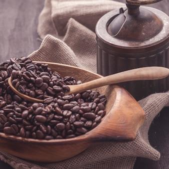 Chicchi di caffè arrostiti in ciotola di legno.