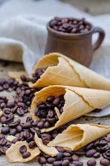 Chicchi di caffè arrostiti in una tazza di ceramica e coni di cialda di zucchero su una parete di legno