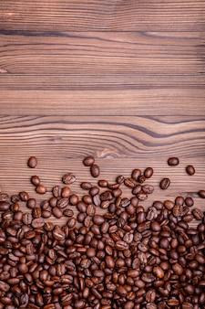 Chicchi di caffè arrostiti su un fondo di legno marrone con copyspace.