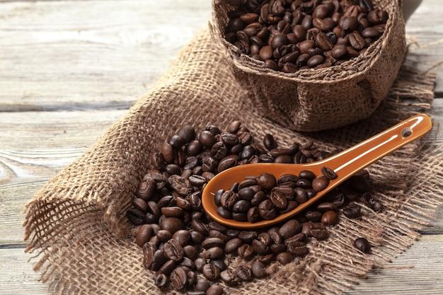 Chicchi di caffè arrostiti su un pavimento di legno