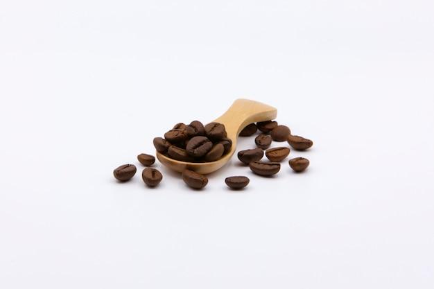 Chicchi di caffè arrostiti sul cucchiaio di legno isolato su priorità bassa bianca.