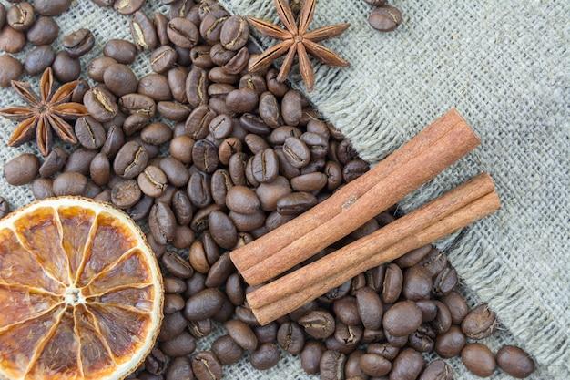 Chicchi di caffè, bastoncini di cannella sparsi sulla tela.