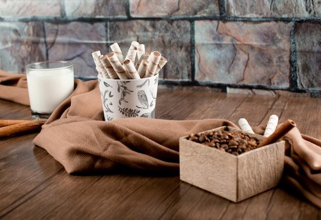 Chicchi di caffè, bastoncini di cialda e un bicchiere di latte avvolto con una sciarpa su un tavolo di legno