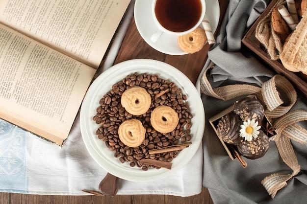 Chicchi di caffè, biscotti, praline e una tazza di tè