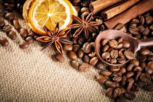 Chicchi di caffè, caffè macinato e cannella su tela da imballaggio.