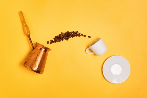 Chicchi di caffè che cadono dal cezve turco nella tazza del caffè espresso, concetto di fabbricazione e di bere del caffè.