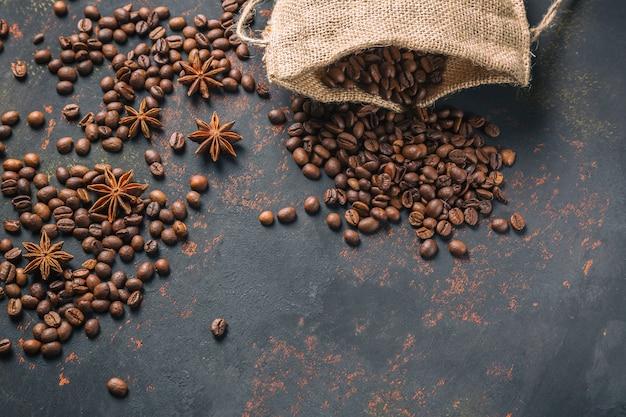 Chicchi di caffè con anice di spezie e sacco di iuta sulla superficie di pietra arrugginita