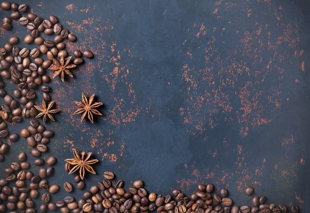 Chicchi di caffè con anice di spezie sul fondo arrugginito della superficie della pietra