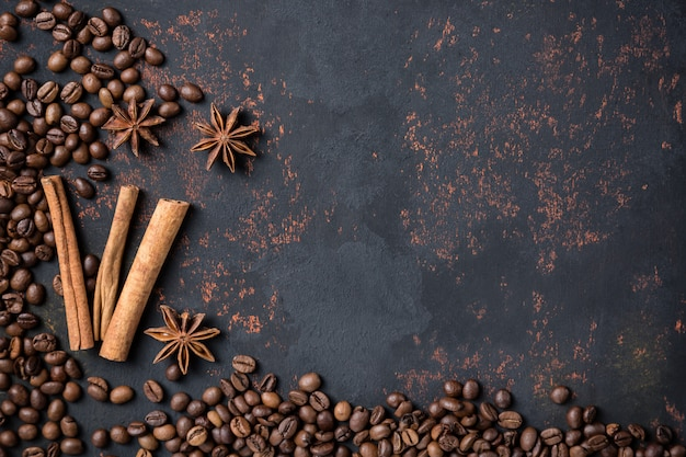 Chicchi di caffè con bastoncini di anice e cannella di spezie sul fondo arrugginito della superficie della pietra