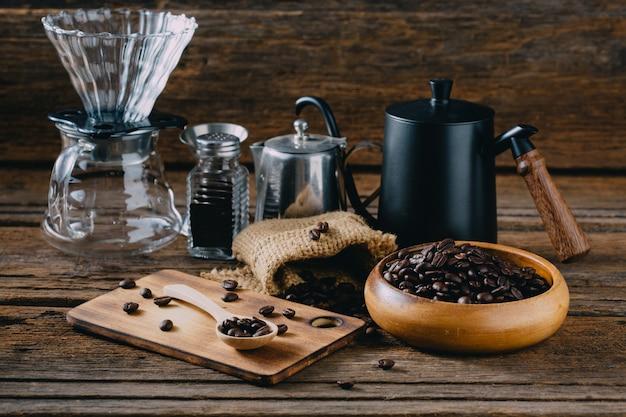 Chicchi di caffè con caffè americano accessorio sul tavolo di legno
