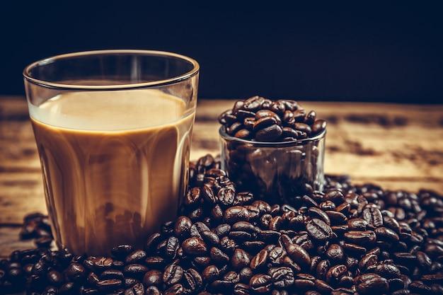 Chicchi di caffè con caffè caldo su legno vecchio