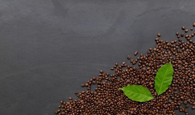 Chicchi di caffè con foglie su superficie nera