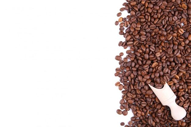 Chicchi di caffè con il cucchiaio isolato su un bianco