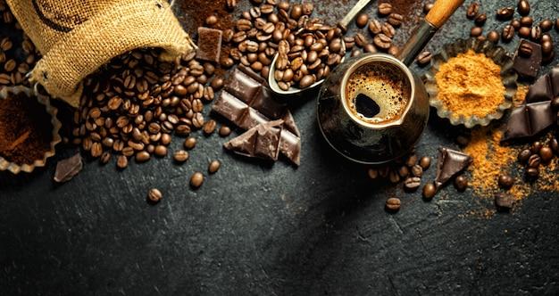 Chicchi di caffè con oggetti di scena per fare il caffè