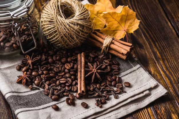 Chicchi di caffè con spezie e foglie di autunno