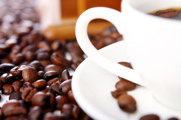 Chicchi di caffè con tazze bianche
