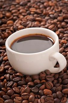 Chicchi di caffè con una tazza bianca