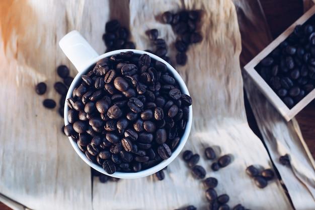 Chicchi di caffè con una tazza sul tavolo